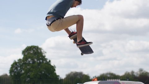 Skateboarder does a high ollie jump from a ramp, in slow motion
