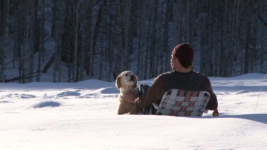 Man petting golden retriever and drinking a beer while sitting in lawn chair out in the snow