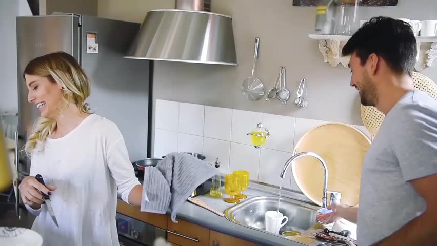 Cheerful young couple having fun together while washing dishes in kitchen.  | Shutterstock HD Video #26042438
