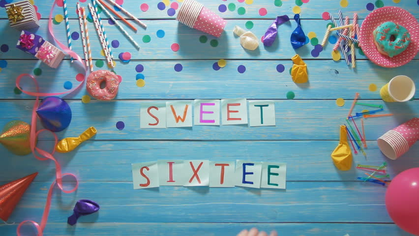 Top view man puts words Sweet Sixteen on the table with birthday decoration