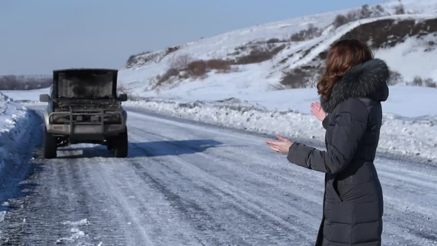 A broken car with an open hood on a winter road in the wilderness and a girl driver swears and grabs herself by the hair | Shutterstock HD Video #26069228