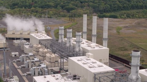 AERIAL: Flying above contemporary efficient geothermal power plant facility using natural gas to produce electricity. High temperatures deep underground generating steam for clean, sustainable power