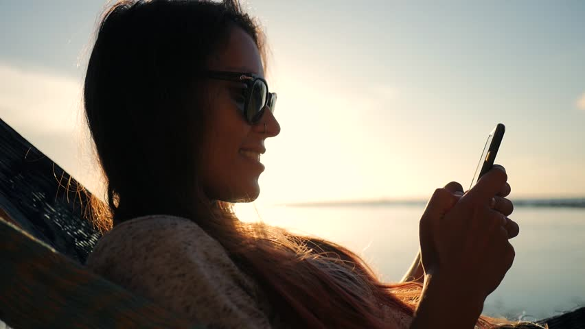 Young Smiling Mixed Race Tourist Girl in Sunglasses Using Mobile Phone in Hammock at the Beach near the Sea with Beautiful Sunset on Background. Koh Phangan, Thailand. HD Slowmotion.