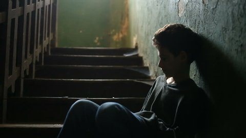 The boy is sitting on the steps of an abandoned porch. The concept of children's drug addiction, vagrancy, homelessness
