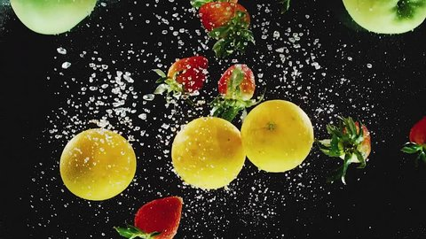 A lot of oranges, apples, strawberries falling into water in slow motion