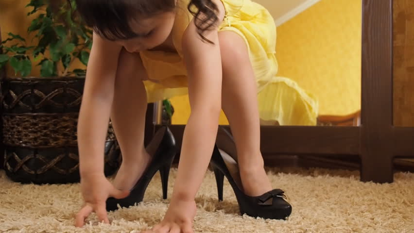 A little girl is playing with her mother's shoes. The legs of a small child in adult shoes. A child in high heels. Slow motion.