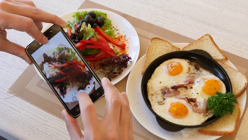 KHERSON, UKRAINE - APR 20, 2017: Food Photo Man Take Pictures Of Scrambled Eggs With Bacon And Vegetables Salad Via Mobile Smartphone