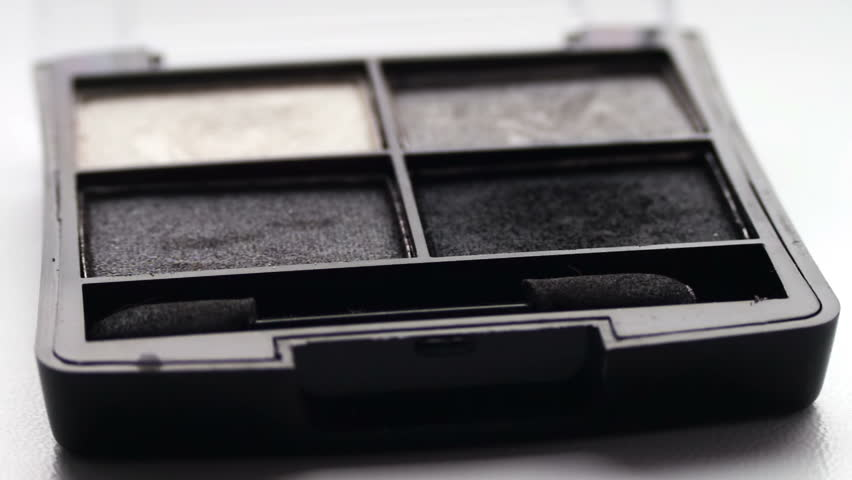 Close up of makeup Eyebrow brush moving over eye shadows.Gray shades of eyeshadow, Close-up view of brush running through the shadows,eye shadow palette for cosmetics,Using eye shadow with brush