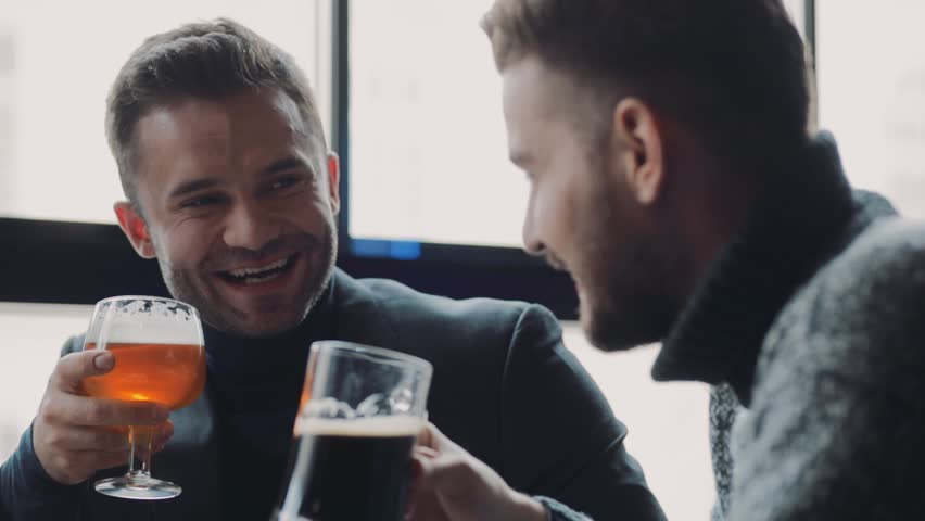 A company of handsome male friends having conversation, they are laughing, joking, toasting and drinking beer. Weekend activities, friends forever. Men's club, hobby.