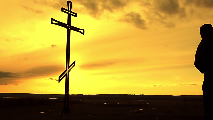 Silhouette man on top of the mountain looking with hope at the Christian Cross. A man making a confession to the cross, background sunset. #26157788