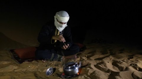 Tuareg man making tea in a desert at night