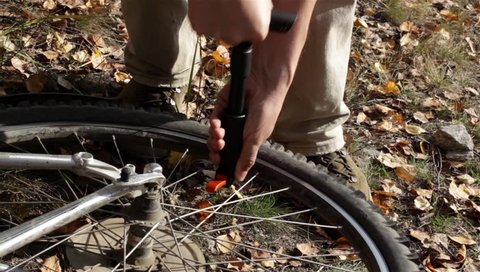 Man inflating tire on bicycle and tighten the nipple