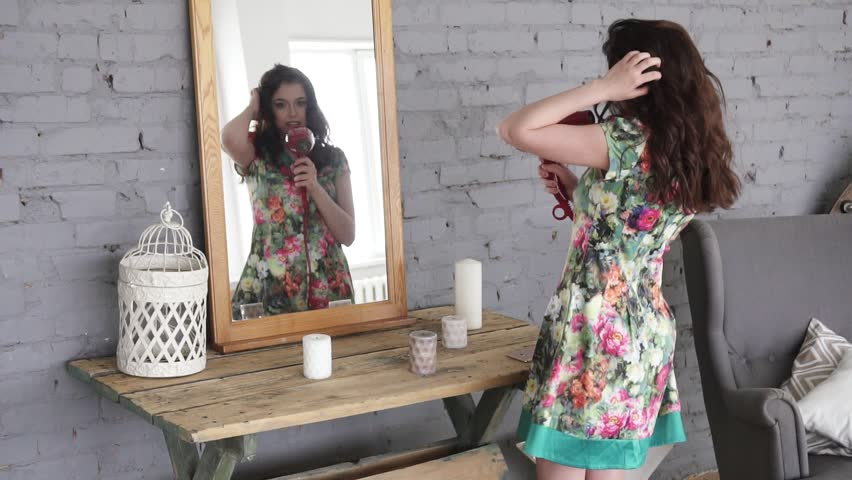 The girl is going to a romantic meeting. An attractive girl dances in front of a mirror and sings in a hairdryer like a microphone. | Shutterstock HD Video #26207618