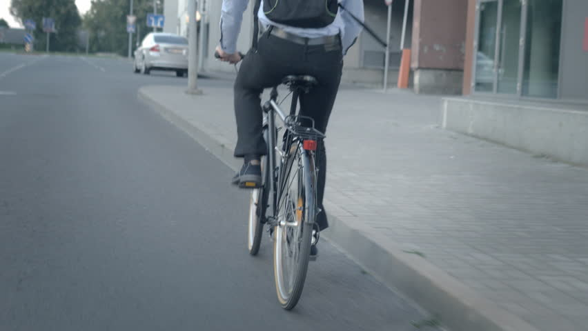 Close-up of formally dressed commuter pedaling on the street. Man traveling to work and maintaining a healthy lifestyle. | Shutterstock HD Video #26214908