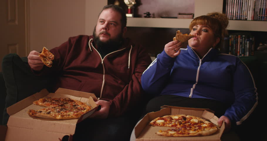 4K Overweight couch potato couple eating takeaway pizza in front of the TV | Shutterstock HD Video #26224958