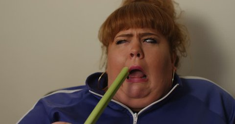 4K Unhappy overweight woman on a diet trying to force herself to eat a stick of celery. Funny dieting concept.