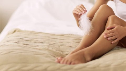 people, beauty, depilation, epilation and bodycare concept - beautiful woman sitting on bed and with feather touching bare legs at home bedroom