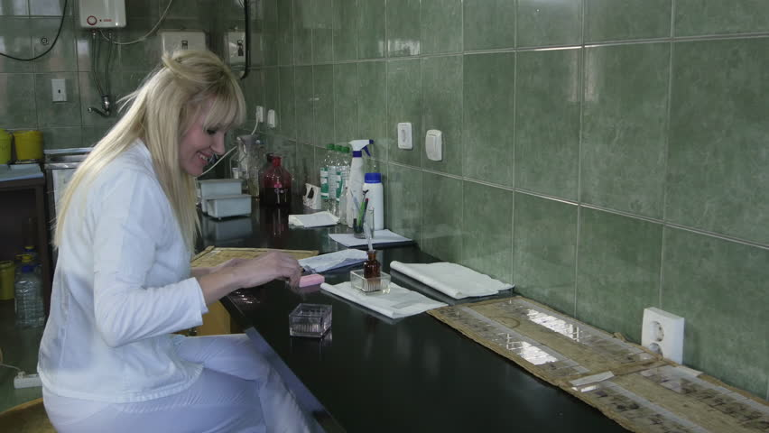 Female lab technician in white uniform and protective gloves sitting at a table and using chemicals from petri dishes to analyze a tissue samples for pathology tests, woman pouring and mixing fluids | Shutterstock HD Video #26244623