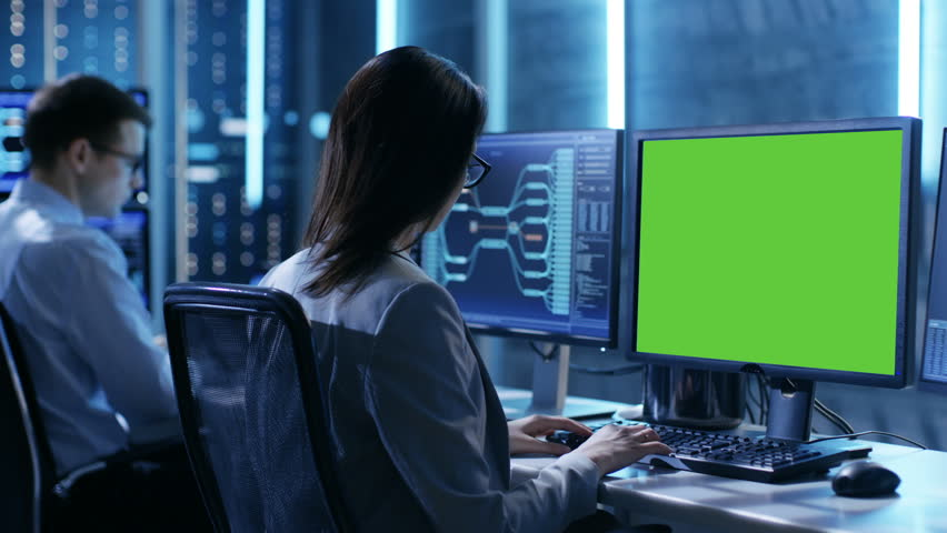 Female Controller/ Operator Working at His Workstation with Multiple Displays (Green Screen Mock-up). Possible Power Plant/ Airport Dispatcher/ Dam Worker/ Government Surveillance/ Space Program.