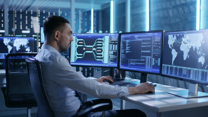 System Security Specialist Working at System Control Center. Room is Full of Screens Displaying Various Information. He Shares His Opinions with Colleagues. Shot on RED EPIC-W 8K Helium Cinema Camera. | Shutterstock HD Video #26262158