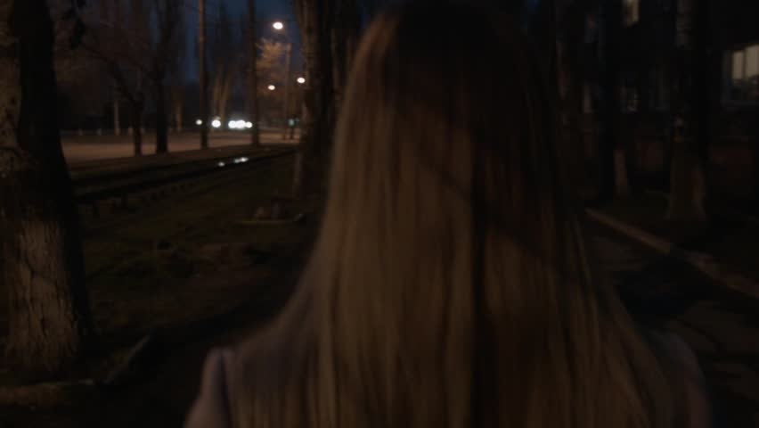 A woman walks along the street at night. A girl on roller skates is going to meet her. We follow the blonde from behind, which is walking along the street.