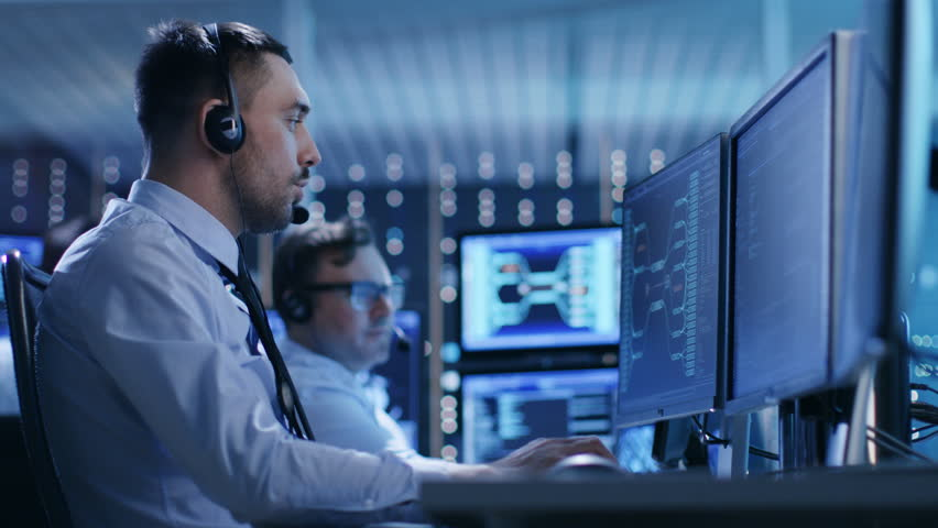 In the System Control Center Technical Support Team Gives Instructions with the Help of the Headsets. Possible Air Traffic/ Power Plant/ Security Room Theme. Shot on RED EPIC-W 8K Helium Cinema Camera