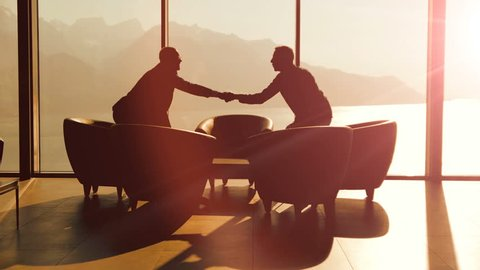 business partners meeting inside modern lobby hall chatting over contract agreement deal. businessman handshaking scene background