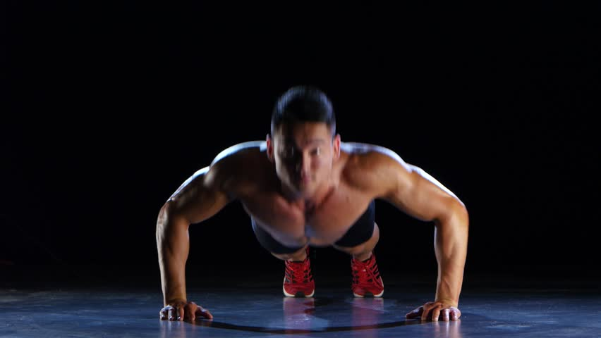 Asian athlete push ups, squeezes from the floor, he is strong and hardy. Black background | Shutterstock HD Video #26265638