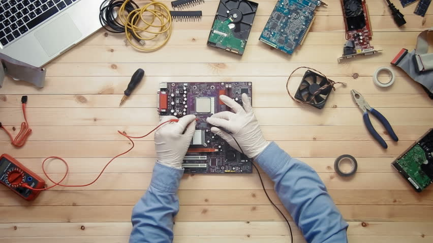 Top view computer technician testing motherboard at wooden desk with tools and electronic components | Shutterstock HD Video #26268368