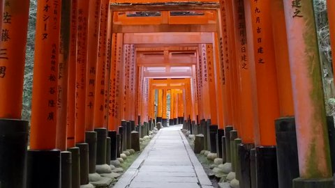 POV SLOW MOTION: Walking inside Fushimi Inari Shrine or Fushimi Inari Taisha, a Shinto shrine in Kyoto, Japan. A Japanese monument, famous for its thousands of vermilion torii gates.