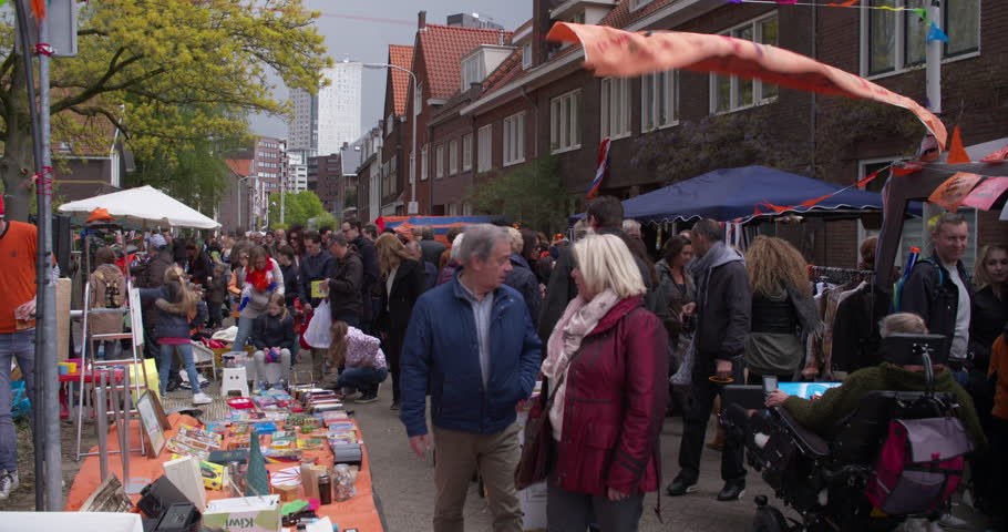 EINDHOVEN, NETHERLANDS - APRIL 27, 2017: Dutch people with orange clothes strolling at a free secondhand flea market on Kings day