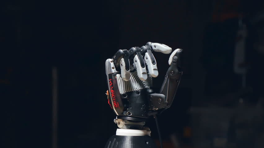 The camera is slowly moving around the robot hand, showing how it is opening the fingers. The thumb is moving to the right.