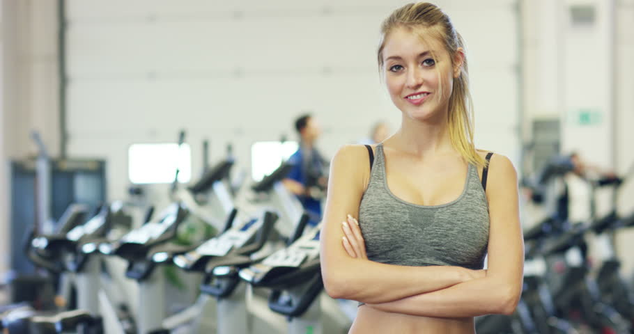 462ab6156d1fac Young beautiful girl in the gym, stands smiling after coaching, satisfied  and relaxed, proud of her achievements. Concept: love sports, to attend a  gym, ...