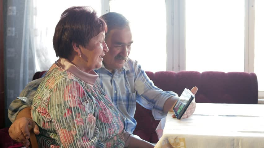 An elderly couple communicates with their grandchild by video linking the tablet. A man and a woman are talking to relatives. | Shutterstock HD Video #26312372