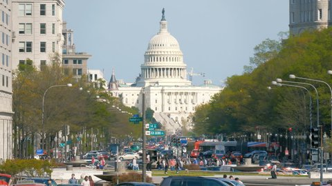 WASHINGTON, DC - APRIL 12: Capitol Hill with city traffic and Capitol Building background on April 12, 2017. The Unites States Capital Building is the home of Congress of the U.S. federal government.