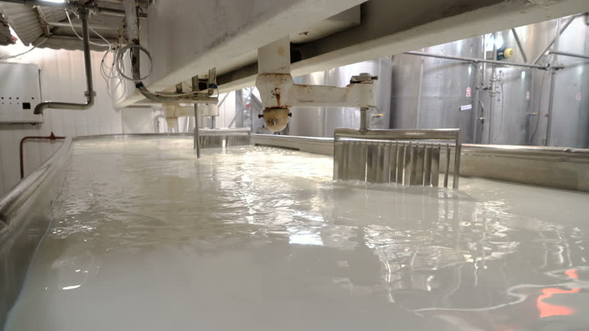 Mixing the milk in a large stainless steel tank. Dairy plant.