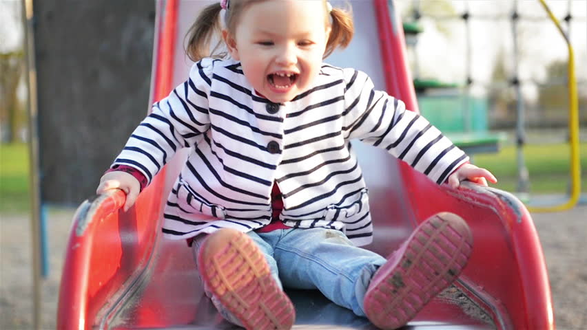 Funny Cute Girl with Two Ponytails is Playing on Red Slide. Joyous Female Child in Striped Jacket Having Fun on Playground in the Park.
