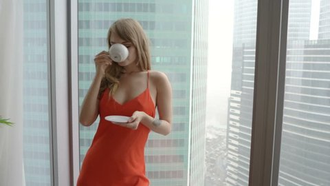 Young woman wearing red nightdress drinking cup of tea and standing near the window