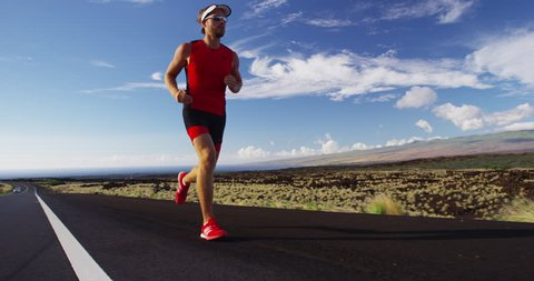 Triathlon - Triathlete man running in triathlon suit training for ironman race. Male runner exercising in beautiful landscape on road on Big Island Hawaii. RED EPIC SLOW MOTION.