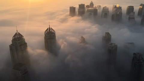 Rare early morning winter fog above the Dubai Marina skyline and skyscrapers ahead of sunrise. Dubai, UAE - 05/DEC/2016