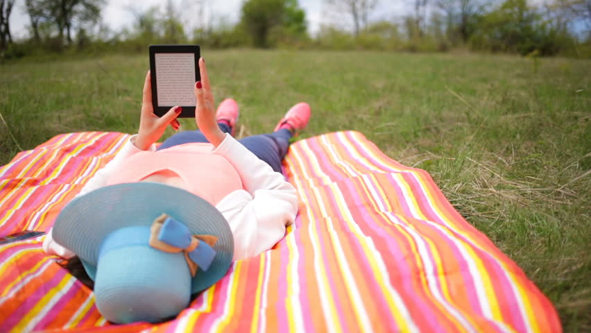 Attractive young woman uses e-book/tablet lying down on a colourful blanket in the park. Modern lifestyle using portable mobile devices everywhere people go. Reading e-mail Slide (slider) shot. Hat.