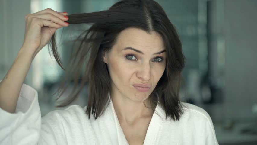 Unhappy woman on bathrobe checking her hair in mirror in bathroom