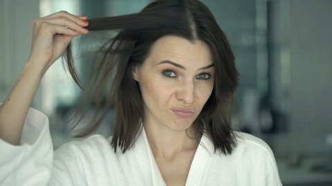 Unhappy woman on bathrobe checking her hair in mirror in bathroom