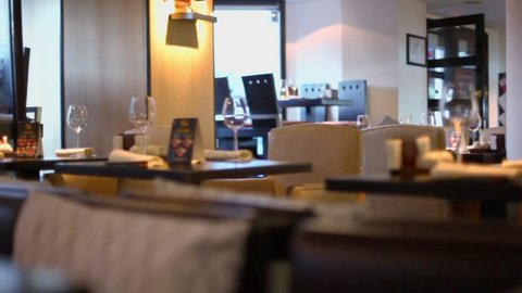 Several clients sit behind water walls in resturant, panoramic motion