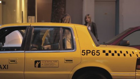 Two women entering NYC Yellow taxi cab. Yellow taxicabs can pick up passengers anywhere in New York