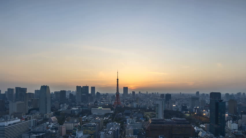 4k time lapse of night to day sunrise scene at Tokyo city skyline with Tokyo Tower. Tilt down
