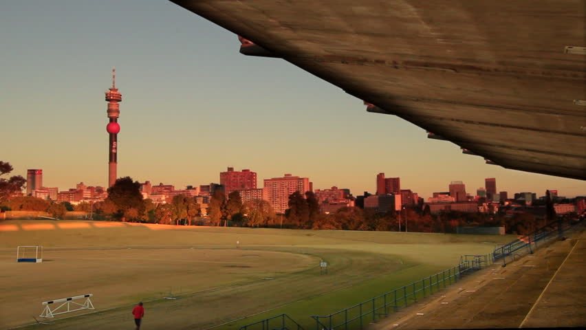 The skyline of Johannesburg, South Africa at sunset from a sports stadium. Johannesburg is one of Africa's largest cities and is the hub of South Africa's gold mining and banking industry.