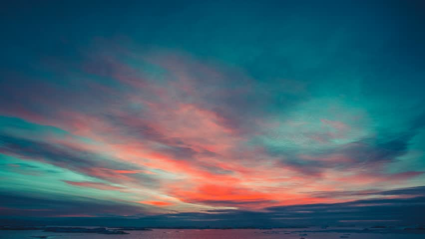 Antarctic Nature. Beautiful colorful sunset cloudy sky. Bright orange clouds reflected in ocean. Majestic polar landscape. Beauty world, holiday, sport and recreation. Travel background. Time lapse 4K