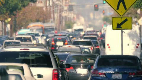 Telephoto shot of city street crowded with cars stuck in traffic jam on a hot day, seen through hot air turbulence. Los Angeles, California. 4K UHD, slow motion.