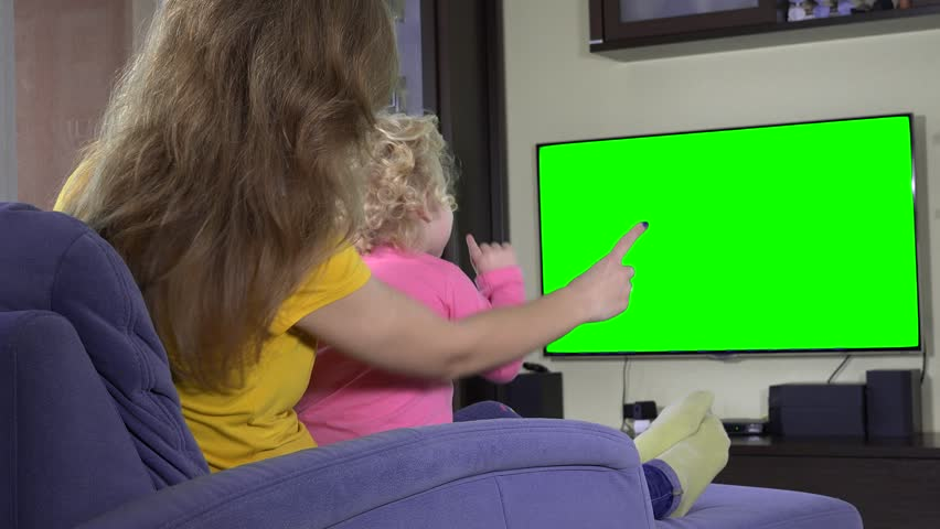 Young mother with her child girl watch tv and show finger. Green chroma key screen. Static shot. 4K UHD